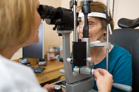 slit: Female optometrist examining senior womans eyes with slit lamp in eye clinic Stock Photo