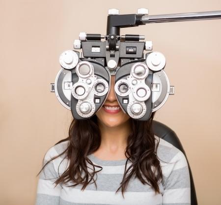 Gelukkig jonge vrouw kijkt door phoropter tijdens oogonderzoek