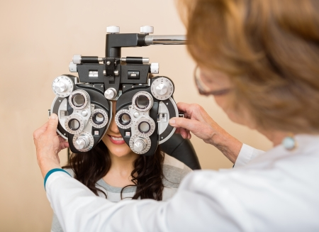 Senior female optometrist adjusting phoropter for young patient in store