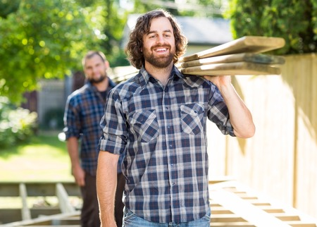 Happy mid adult carpenter with coworker carrying wooden planks outdoors photo
