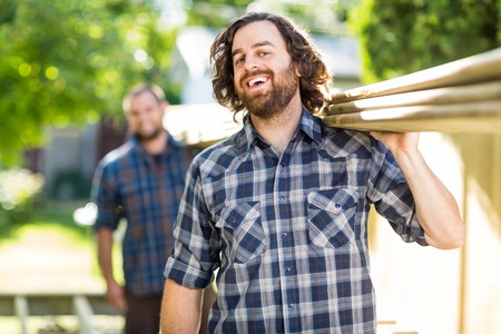 Mid adult carpenter with coworker carrying wooden planks while laughing outdoors photo