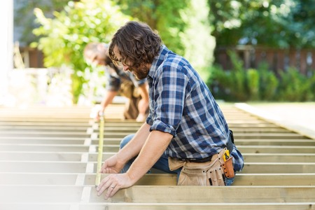 porches: Profile shot of mid adult carpenter measuring wood with tape while coworker assisting him at construction site