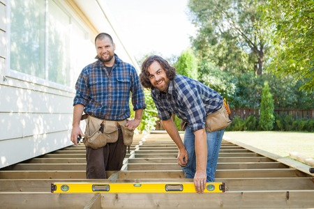 porches: Portrait of happy construction worker checking level of wood with spirit level while standing with coworker at it