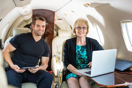 Portrait of confident business people with laptop and digital tablet on private jet photo
