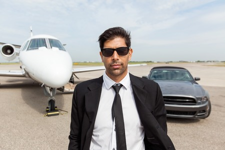 wealthy lifestyle: Portrait of confident male entrepreneur in front of car and private jet