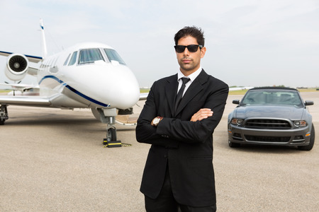 Portrait of confident businessman standing in front of car and private jet at terminal photo