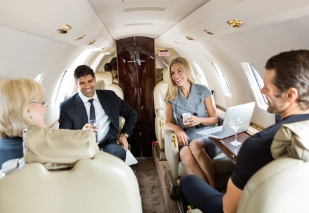 corporate jet: Confident business professionals having drinks on a private jet Stock Photo