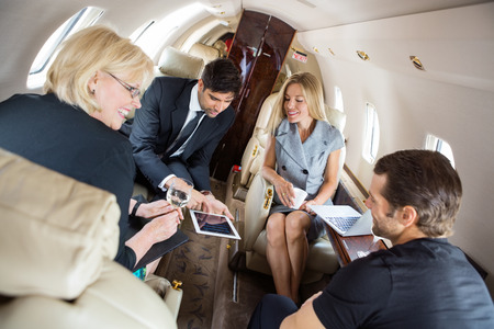 Businessman showing presentation on digital tablet with colleagues in corporate jet Stock Photo