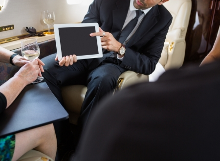 Cropped image of businessman showing digital tablet to partners in private jet photo