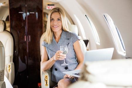 Portrait of beautiful businesswoman having wine in corporate jet photo