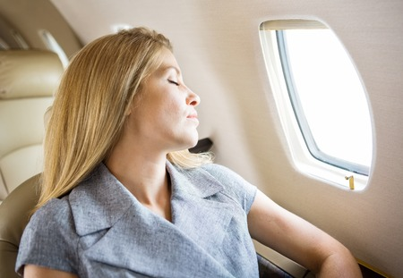 Relaxed mid adult businesswoman sleeping in private jet