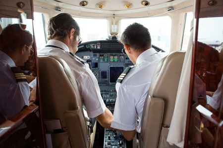 Rear view of pilot and copilot in cockpit of corporate jet photo