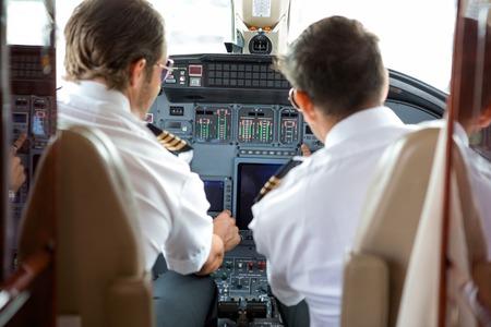 パイロットと副操縦士ビジネス ジェットのコントロールの動作の背面図 写真素材