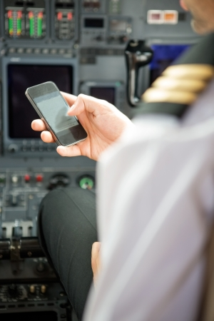 Pilots using smartphone in cockpit of private jet photo