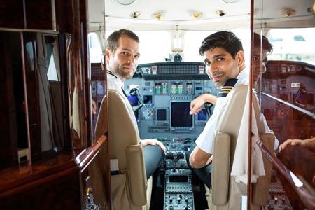 first plane: Portrait of confident pilots in corporate plane cockpit