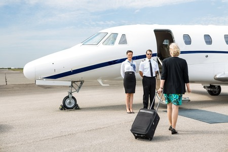 Rear view of businesswoman with luggage walking towards private jet while pilot and airhostess standing by photo