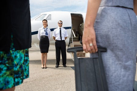 Full length of pilot and airhostess standing near private jet with business people in foreground photo