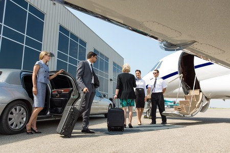 wealthy: Business professional about to board private jet while airhostess and pilot greeting them Stock Photo
