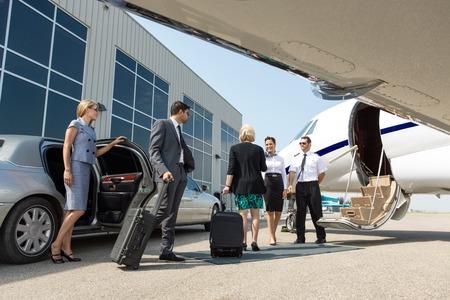 millonario: Profesional de negocios a punto de abordar un jet privado mientras azafata y piloto de saludarlos Foto de archivo