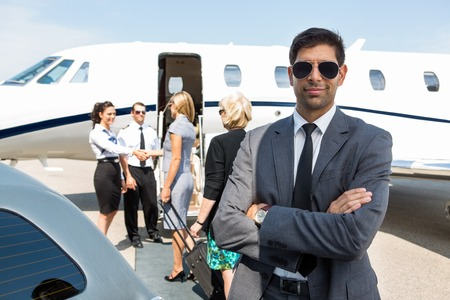 airhostess: Portrait of confident young businessman with airhostess and pilot greeting businesswomen against private jet Stock Photo