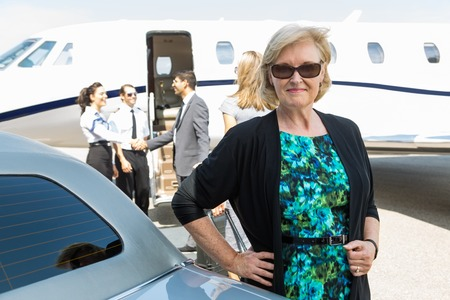 Portrait of confident businesswoman with airhostess and pilot greeting business people near private jet photo