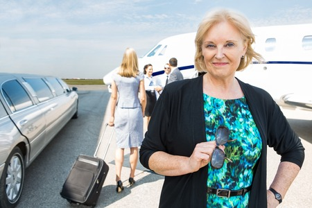 Portrait of confident businesswoman with limousine and private jet in background photo