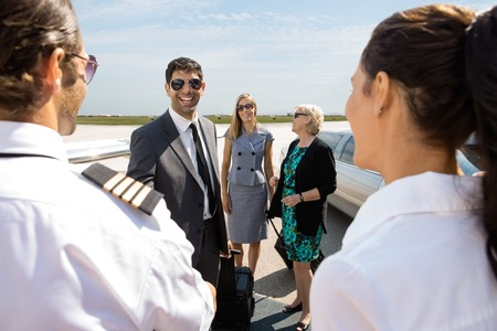 Happy businessman with colleagues greeting pilot and airhostess at airport terminal photo