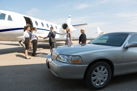 corporate jet: Business professional greeting airhostess and pilot near private jet and limo