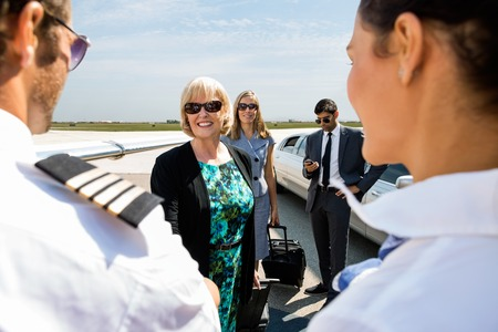 Happy mature businesswoman with colleagues greeting airhostess and pilot at airport terminal photo