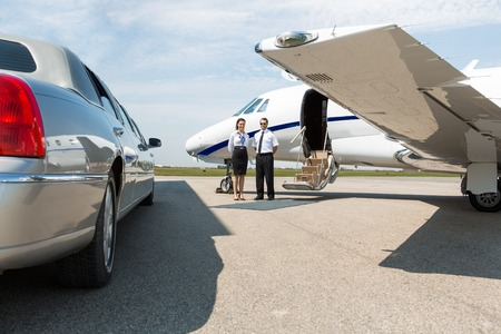 Airhostess and pilot standing neat limousine and private jet at airport terminal photo