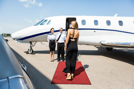 limo: Rear view of rich woman walking towards private jet while pilot and stewardess standing at airport terminal