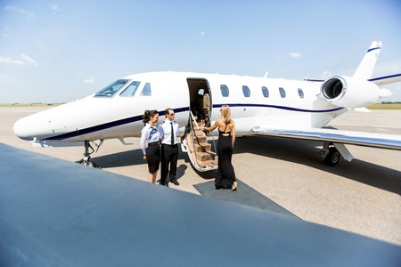 Elegant woman boarding private jet with airhostess and pilot at airport terminal photo