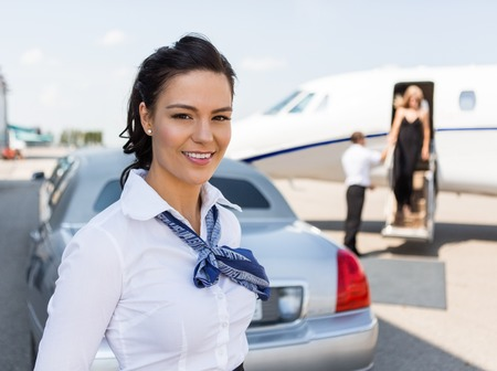 Portrait of beautiful stewardess standing against limousine and private jet at airport terminal photo