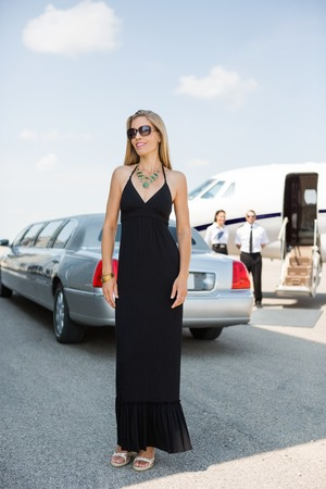 Full length of beautiful woman in elegant dress standing against limousine and private photo
