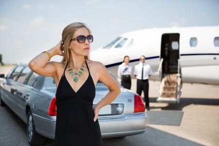 Femme riche en robe élégante debout contre limousine et privé à la borne
