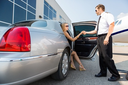 Full length of pilot helping woman stepping out of car at airport terminal Stock Photo