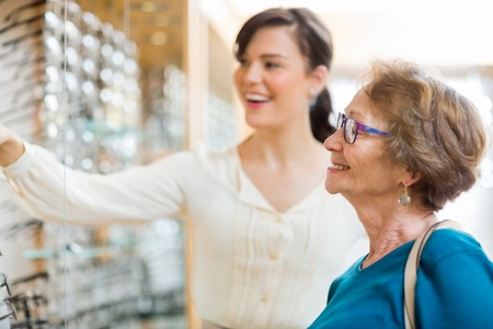 spectacle: Young woman assisting senior female customer in selecting glasses at store