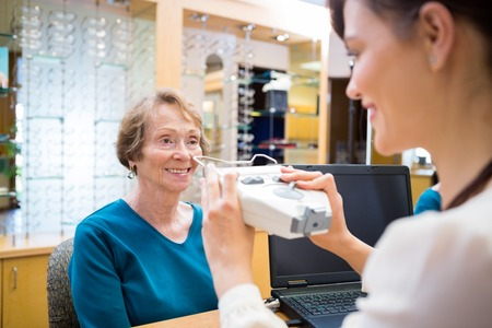Happy senior woman getting an eye test from ophthalmologist in store photo