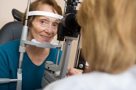 slit: Retrato de la mujer mayor que tiene prueba del ojo con l�mpara de hendidura en la tienda