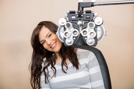examen de la vista: Retrato de mujer joven feliz sentado detr�s phoropter durante examen de la vista Foto de archivo