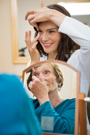 Female eyecare doctor teaching senior woman to insert contact lens in optician store photo