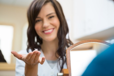 lentes de contacto: Retrato de un optometrista que muestra la lente de contacto de mujer joven en la tienda de óptica