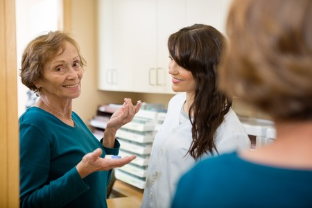 Optometrist looking at senior woman holding contact lens on finger in store photo