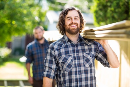 Portrait of happy mid adult carpenter with coworker carrying wooden planks outdoors photo