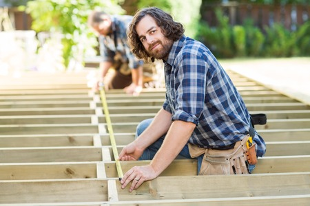 Side view portrait of mid adult carpenter measuring wood with tape while coworker assisting him at construction site