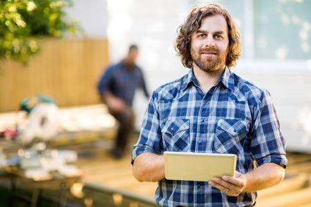 craftsman: Retrato de mediados trabajador manual adulto que sostiene la tablilla digital con compañero de trabajo en segundo plano en el sitio de construcción Foto de archivo