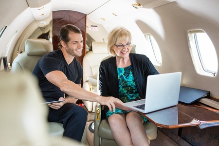 Businessman with female colleague discussing over laptop on private jet photo