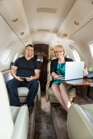 Portrait of confident business people with laptop and digital tablet in corporate jet photo