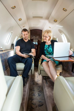 Young businessman showing something to female colleague on digital tablet in private jet photo
