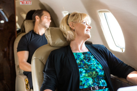 corporate airplane: Happy mature businesswoman with man sleeping behind on private jet Stock Photo